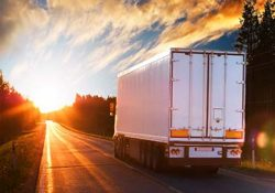 commercial truck driving into sunset