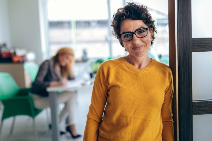 woman with yellow shirt leaning on door, woman in background sitting at desk blurred